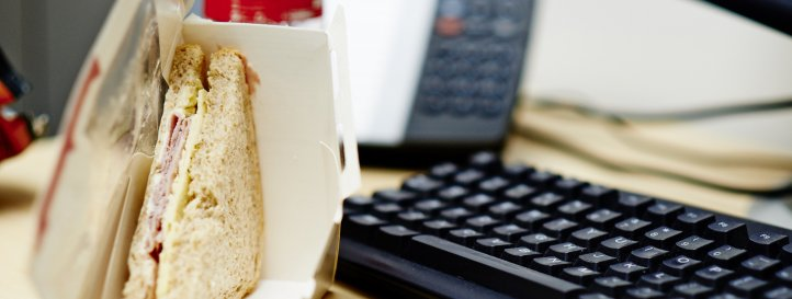 Office desk with computer keyboard and abandoned sandwich